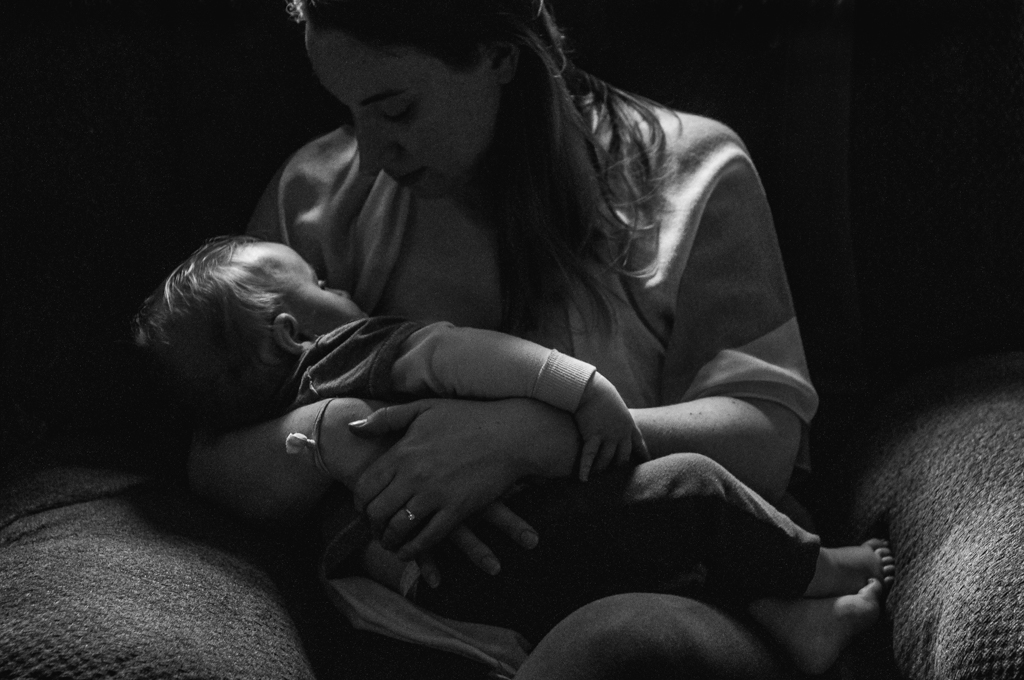 breastfeeding mother and her toddler son in black and white